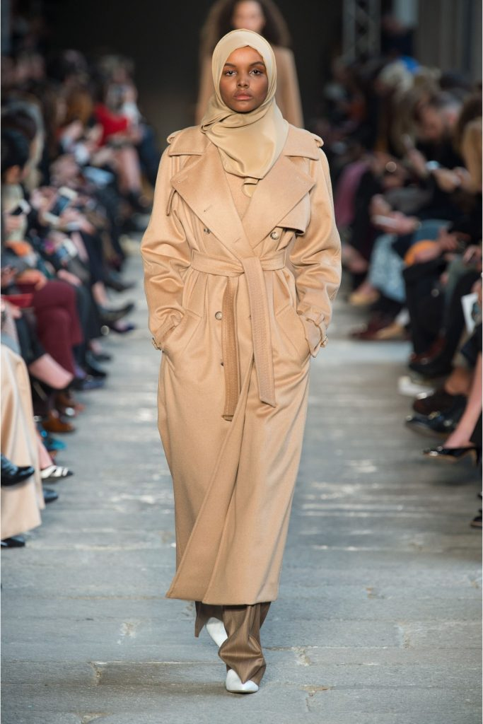 A catwalk model wearing a long, beige raincoat and matching hijab