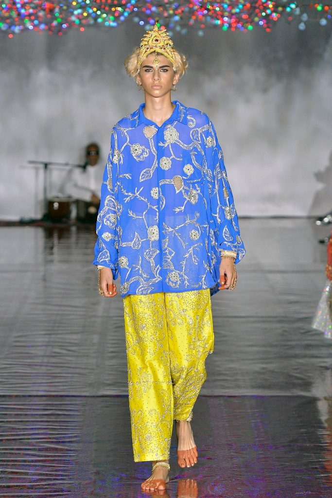 A catwalk model wearing a blue floral patterned shirt and gold trousers