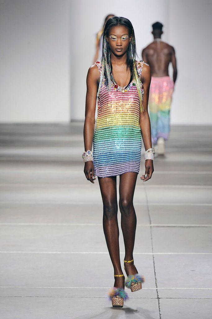 A catwalk model wearing a rainbow sequined dress