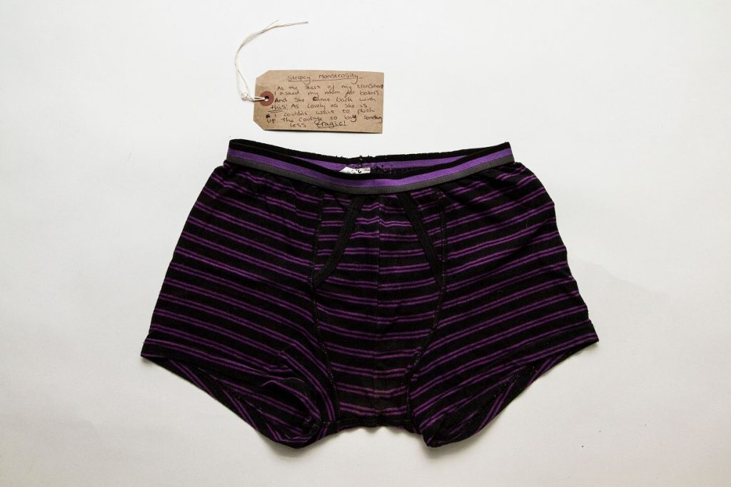 Photo depicting a pair of black boxing shorts with a purple band by Katy Davies, Fashion Space Gallery, London College of Fashion.